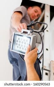 Electrician team handing light making good workflow.