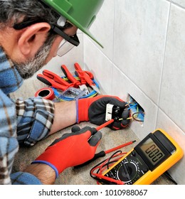 Electrician technician with gloves and safety instruments fixes the electric cable to the socket of a residential installation.