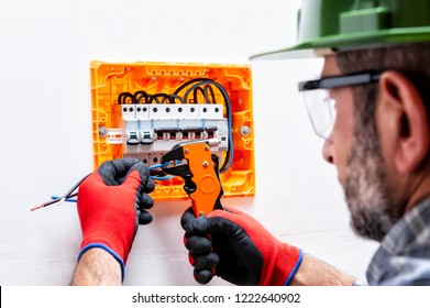 Electrician technician with helmet, goggles and gloves protected hands, works with wire stripper in a residential electrical panel.