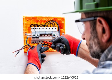 Electrician technician with helmet, goggles and hands protected by gloves with screwdriver fastens the cable in a residential electrical panel.
