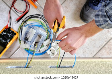 Electrician technician at work with scissors in a residential electric installation