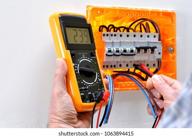 Electrician technician working on a residential electrical panel, measures the voltage on the terminals of the thermal magnetic circuit breaker