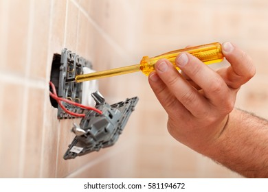 Electrician testing for electricity in electrical wall fixture with a voltage tester or phase indicator