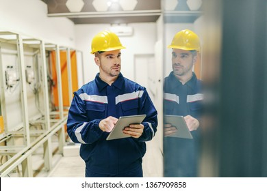 Electrician in uniform and helmet on head using tablet and checking on dashboard in control room in heavy industry plant.