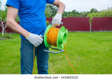 An electrician is unrolling an extension cord on the coil in the house backyard. Cleaning of the territory.