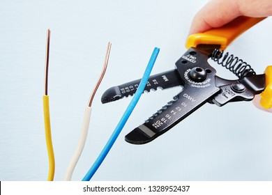 Electrician uses the wire stripper cutter to remove of insulation from the tip of each of the wires during electrical wiring services, close-up.