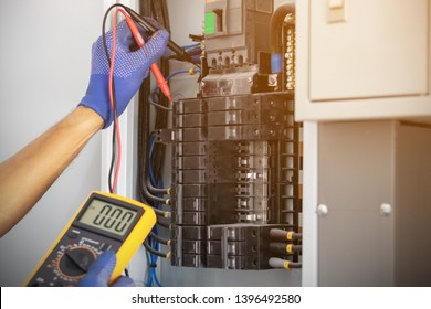 Electrician is using a digital meter to measure the voltage at the circuit breaker control cabinet on the wall.