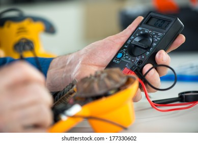 Electrician using Digital Voltmeter for Testing Voltage on old hair dryer. Close Up. Selective focus.