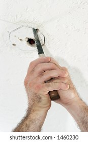 An electrician with using a saw to cut a hole in the ceiling to put a fan box. Work is being performed by a licensed master electrician.