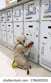 The electrician wear arc flash suit, electrical safety gloves and high voltage insulating boots to opening for switching-device track operation of circuit breaker panel