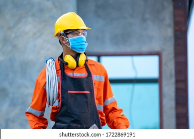 Electrician wearing protective mask to Protect Against Covid-19 and checking production process at the construction site,Engineer,Construction concept,Coronavirus has turned into a global emergency.