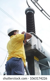 An electrician wearing a safety helmet and glasses, is checking the wiring of electrical equipment (capacitive voltage transformer) in switch yard, substation.