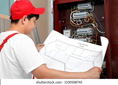 Electrician with wiring diagram indoors