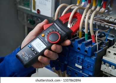 Electrician work concept. Hand with multimeter tester in switchbox