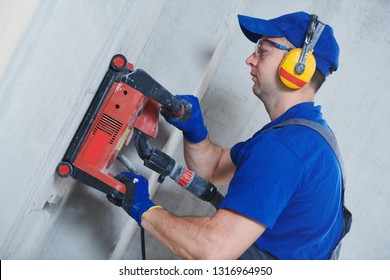 electrician at work. cutting concrete wall for cabling by diamond slitting machine