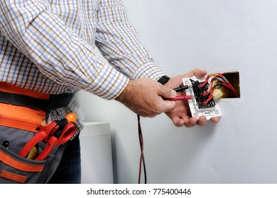Electrician at work on switches and sockets of a residential electrical system.
