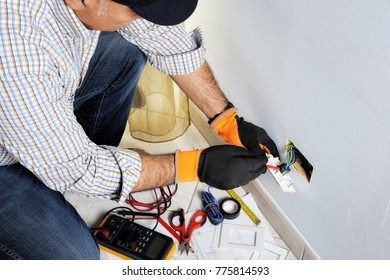 Electrician at work on switches and sockets of a residential electrical system with protective gloves