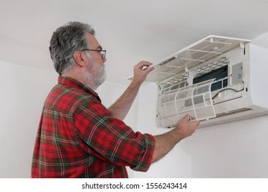 Electrician worker cleaning filter of air condition device in a room