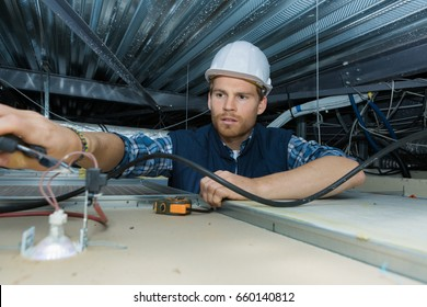 electrician working with electric wires in a factory