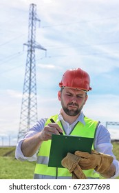 Electrician working in a helmet wearing gloves stand in a field