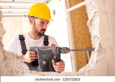 Electrician working with masonry tools wearing protective and safety gear