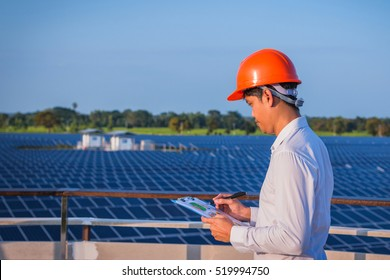 electrician working on checking and maintenance equipment at industry solar power; engineer standing at view point