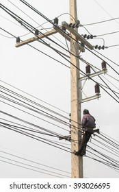 The electrician is working on electric pole