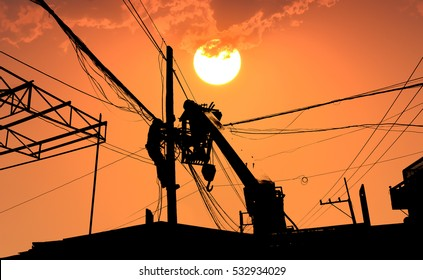 Electrician working on electric pole in sunset background.