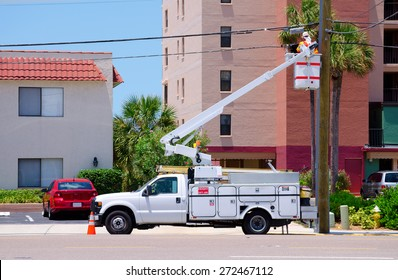 Electrician working on high power lines from a lift on the back of a truck