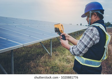 electrician working on maintenance equipment at industry solar power; engineer use IR camera to check temperature loss of solar panel