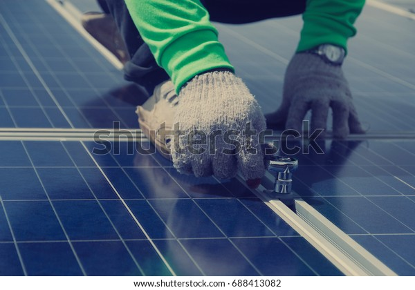 electrician working on  maintenance equipment at solar power plant; electrician swapping  solar panel with solar panel voltage drop