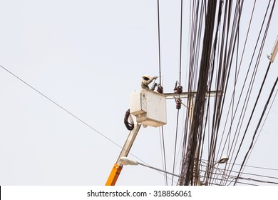 Electrician working repairing the power line on hydraulic platform