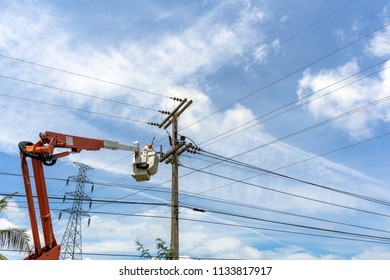 Electrician works on a basket. Technicians are repairing high voltage system.