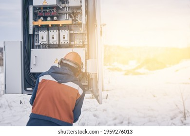 Electrician works in outfit at transformer station, repair and replacement of automatic circuit breaker relay