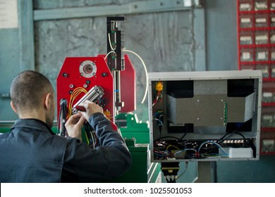Electrician works with parts of energy equipment on plant