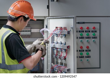 Electrician young people working with wires in the control room of plant.
