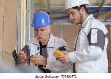 electricians checking socket voltage with digital multimeter