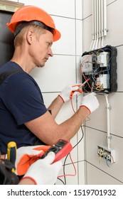 Die Elektriker überprüfen die Spannung an den Endgeräten des elektrischen Zählers. Sie benutzen einen Multimeter.