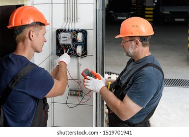 Electricians are checking the voltage at the terminals of the electrical meter. They are using a multimeter.