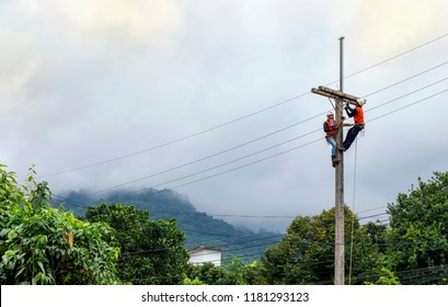 Electricians are climbing on electric pole to maintenance and repair high power lines