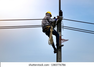 Electricians are climbing on electric poles to install power lines. Electrician lineman repairman worker at climbing work on electric post power pole.