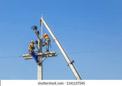 Electricians climbing work in the height on concrete electric power pole with big  crane