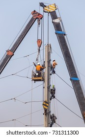 Electricians climbing work in the height on concrete electric power pole and basket with big crane on blue sky background