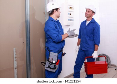 Electricians in front of electrical panel