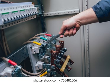 electricians hands testing switches in electric box  electrical panel with  fuses and contactors  background