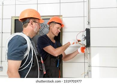 Die Elektriker installieren die Wandverkabelung. Sie verbinden Kabel in der Anschlussdose.