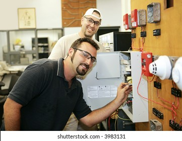 Electricians learning to repair fire alarm systems in a vocational education training class.