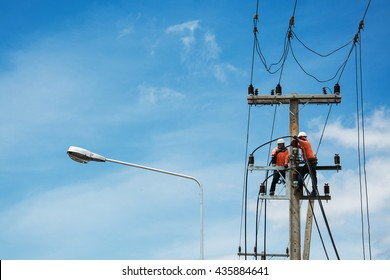 electricians repairing wire of the power line on electric power pole