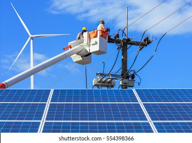 Electricians  repairing wire of the power line on bucket hydraulic lifting platform with solar panels and wind turbines in  power station