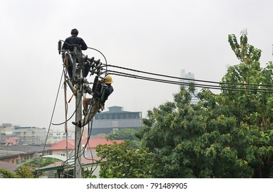 Electricians resting while working to replace the electrical insulator on the electricity pole.
